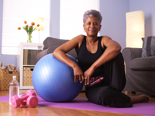 Relaxed lady leaning on exercise ball after workout